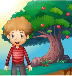 A boy standing in front of the apple tree vector
