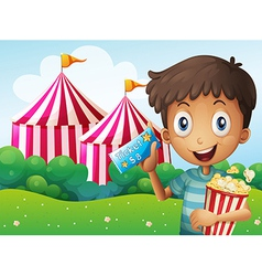 A boy holding a ticket and a pail of popcorn vector image