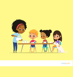 Smiling multiracial children sit at table and have vector
