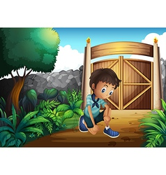 A boy watching the ground inside the gate vector
