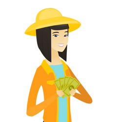 Young happy asian farmer holding money vector