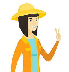 Young asian farmer showing the victory gesture vector