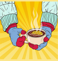 Hands in mittens holding cup with hot tea vector