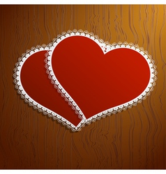 Two lacy red hearts on a wooden background vector