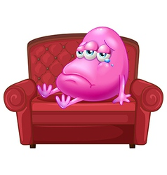 A crying monster sitting on a red sofa vector