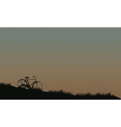 Silhouette of bike in fields vector