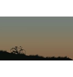 Silhouette of bike in fields vector