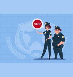 Two police women holding stop sign wearing uniform vector