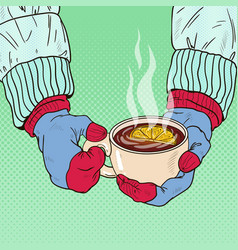 Hands in mittens holding mug with hot tea vector