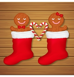 Loving couple of gingerbread cookies in red socks vector