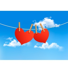 Two hearts hanging on a rope in front of a sky vector