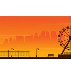 Silhouette amusement park at sunset vector