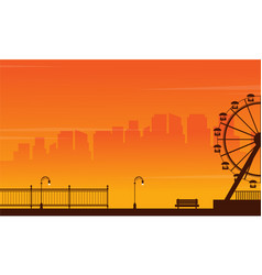 Silhouette amusement park at sunset vector