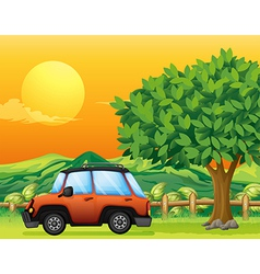 An orange vehicle near the big tree vector image vector image