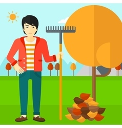 Man with rake standing near tree and heap of vector image
