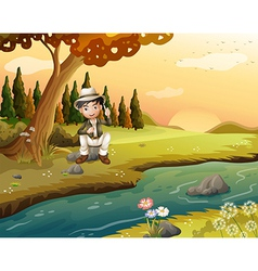 A boy sitting near the riverbank vector image