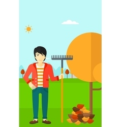 Man with rake standing near tree and heap of vector