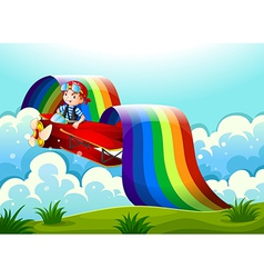 A plane with a young boy and a rainbow in the sky vector image