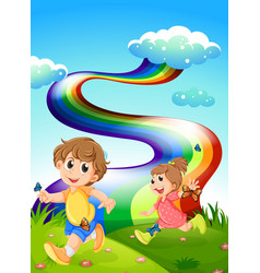 Kids walking at the hill with a rainbow in the sky vector image