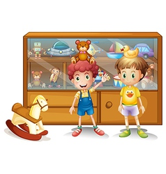 Two young boys in front of a cabinet with toys vector image vector image