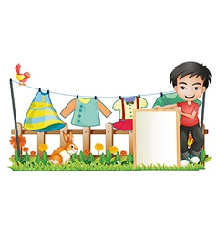 A boy with a frame in front of the hanging clothes vector