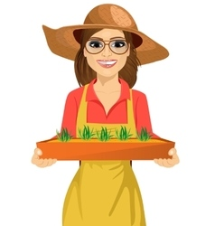 Young farmer woman holding box of seedlings plants vector