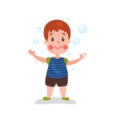 cute cartoon redhead little boy having fun playing vector image vector image