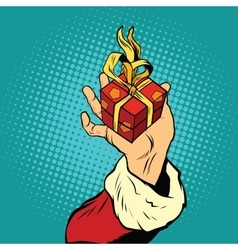Hand of Santa Claus with gift vector image