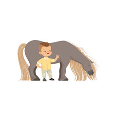Cute smiling little boy standing next pony horse vector