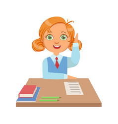 cute schoolgirl sitting at the desk and raising vector image vector image