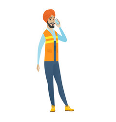 Young hindu builder talking on a mobile phone vector