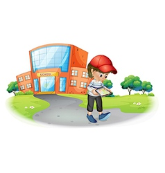 A boy holding a gadget near the school vector image vector image