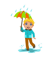 Boy under raindrops with umbrella kid in autumn vector
