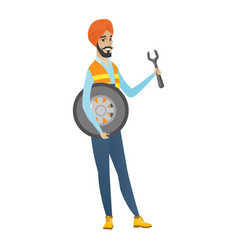 Young hindu mechanic with tyre and spanner vector