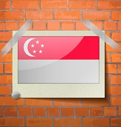 Flags Singapore scotch taped to a red brick wall vector image