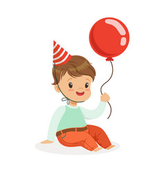 Adorable baby boy wearing a red party hat sitting vector