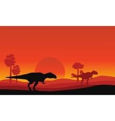 Silhouette of mapusaurus orange sky scenery vector