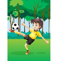 A boy playing soccer at the forest vector