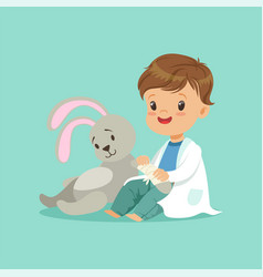 cute baby boy heals paw of toy bunny little vector image vector image