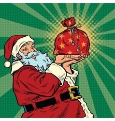 Santa claus with a festive christmas gift bag vector