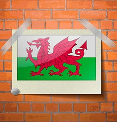 Flags Wales scotch taped to a red brick wall vector image