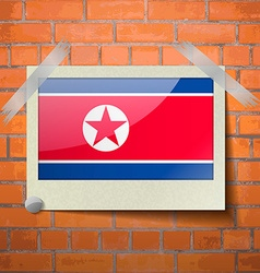 Flags Korea North scotch taped to a red brick wall vector image