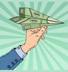 Pop art hand throwing dollar paper plane vector