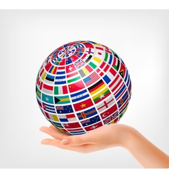 Flags of the world on a globe held in hand vector