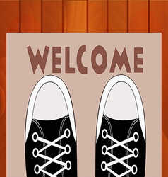 Feet teen in sneakers close up on a doorway rug vector