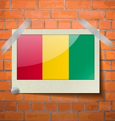 Flags guinea scotch taped to a red brick wall vector