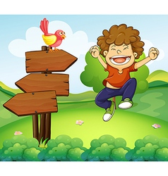 A happy young boy beside the three wooden arrows vector image