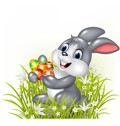 Happy cartoon bunny holding an easter egg vector