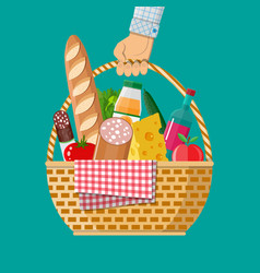 Hand holds wicker picnic basket full of products vector