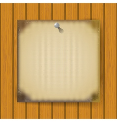 Burnt sheet of paper on a wooden wall vector